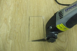 dremel-multi-max-tool-cutting-out-the-back-of-a-cabinet-for-outlet-copy