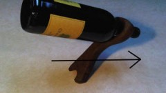 Balancing wine bottle holder image with an arrow