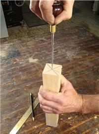 Dimple the center point of a spindle blank using a scratch awl.